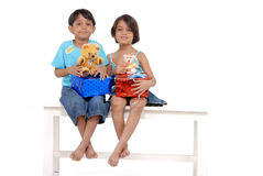 Brother and sister holding gifts and teddy bears. Twins brother and sister sitting on bench holding gifts and teddy bears stock images