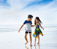Brother sister holding hand walk on the beach Royalty Free Stock Images