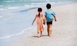 Brother sister holding hand walk on the beach Royalty Free Stock Photos
