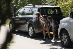 Brother and sister standing between cars trying to run across street. Brother and sister holding hands and standing between cars trying to run across street royalty free stock image