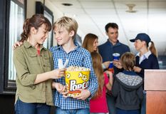 Brother And Sister Holding Popcorn At Cinema Royalty Free Stock Photos
