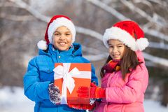 Brother and sister holding present together. Two children celebrating birthday outside royalty free stock image