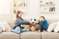 Brother and sister holding soccer ball at home. Cute boy and girl getting ready to play football, sitting on couch, copy space Royalty Free Stock Photos