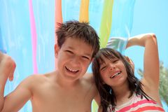 Brother and sister on holiday. Brother and sister have fun with an inflatable swimming mattress on vacation stock photography