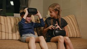Brother with sister at home sitting on the couch playing the game using virtual reality glasses. Happy family stock video