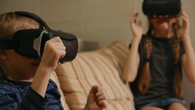 Brother with sister at home sitting on the couch playing the game using virtual reality glasses. Happy family stock footage