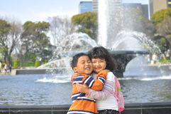 Brother and sister hug each other. The portrait of a brother and his sister hugging each other in front of a fountain opposite to the Japan Imperial Palace Royalty Free Stock Photography