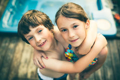 Brother and sister hugging. In bathing suit in front of a jacuzzi Stock Images