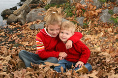Brother and Sister Hugging at the Park stock images