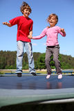 Brother and sister jump on trampoline. Joyful brother and sister jump on trampoline at sunny summer day royalty free stock images