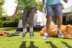 Brother and sister (8-10) jumping in front of incomplete dome tent on garden lawn, low section, front view Royalty Free Stock Image