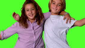 Brother and sister jumping into same shot and embracing on green screen Royalty Free Stock Image