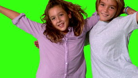 Brother and sister jumping into same shot and embracing on a green screen Royalty Free Stock Photography