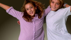 Brother and sister jumping into same shot and embracing on grey background Royalty Free Stock Images