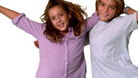Brother and sister jumping into same shot and embracing on white background Royalty Free Stock Images