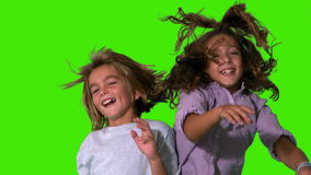 Brother and sister jumping up and crashing on green screen Stock Images