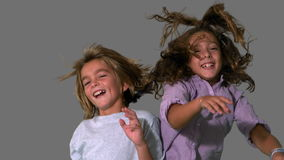 Brother and sister jumping up and crashing on grey background Royalty Free Stock Photos
