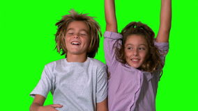 Brother and sister jumping up on green screen Royalty Free Stock Photos
