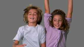 Brother and sister jumping up on grey background Royalty Free Stock Photo