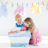 Brother and sister kissing newborn baby Stock Photography
