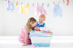 Brother and sister kissing newborn baby Stock Images