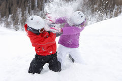 Brother and sister kneeling in snow and having snowball fight royalty free stock photos