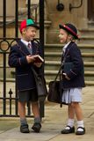 Brother and sister laughing at school gates stock photo
