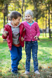 Brother and sister laughing when standing full length in park Stock Image