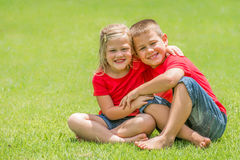 Brother and sister on lawn hugging. Stock Images