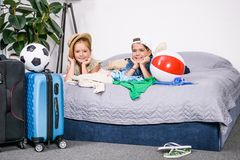brother and sister laying on bed with suitcases going stock image