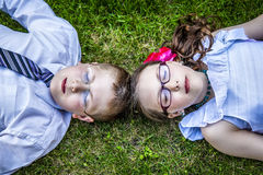 Brother and Sister Laying Down in Grass Eyes Closed Stock Images