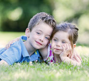 Brother and sister laying in the grass. Outside Stock Image