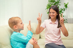 Brother and sister learn sign language at home. Deaf child stock image