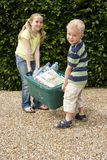 Brother (4-6) and sister (9-11) lifting recycling bin, smiling, portrait Royalty Free Stock Photo