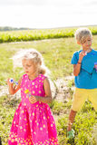 Brother and sister with light curly hair are playing with soap bubbles in the field.  Royalty Free Stock Image