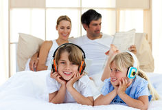 Brother and sister listening music with headphones Stock Images