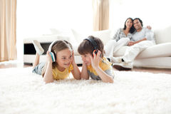 Brother and sister listening music with headphones Stock Photos