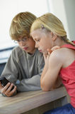 Brother And Sister Looking At Cell Phone Stock Photo