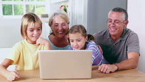 Brother and sister looking at laptop with grandparents Royalty Free Stock Photos
