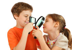 Brother and sister looking through loupes. Brother and sister looking at each other through magnifying glasses isolated on white background; focus on lenses Stock Photos