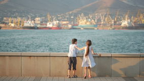 Brother and sister looking at ships in port stock video footage