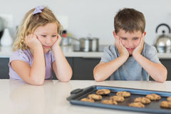 Brother and sister looking at tempting cookies Royalty Free Stock Photo