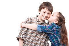 Brother and sister love. Family love. Small pretty girl hugging her older brother and kissing his cheek while he standing and smiling happily isolated on white Royalty Free Stock Photo