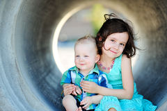 Brother And Sister Love. Six year old girl and her one year old brother smiling and hugging outside Stock Image