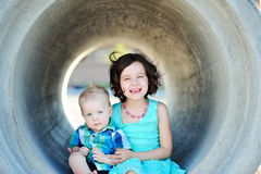 Brother And Sister Love. Six year old girl and her one year old brother smiling and hugging outside Stock Photo