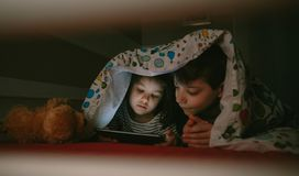 Brothers looking at the tablet in the dark. Brother and sister lying on the bed looking at the tablet in the dark stock image