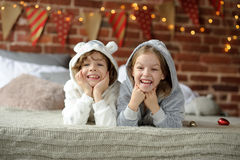 Brother and sister lying on bed in pajamas. Christmas Holidays. Brother and sister lying on bed in pajamas. The bedroom is decorated with Christmas lights. In Royalty Free Stock Photo