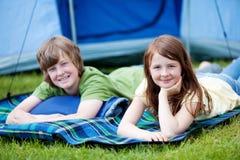Brother And Sister Lying en la manta con la tienda en fondo Fotos de archivo libres de regalías