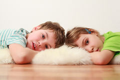 Brother and sister lying on floor on skin Stock Image