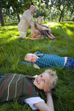 Brother and sister (9-13) lying on grass, parents in background, smiling, portrait royalty free stock photography